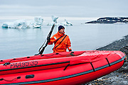 An employee of the Professor Molchanov, a scientific research vessel, keeps watch for polar bears while tourists go ashore in Franz Josef Land, Russian Arctic.