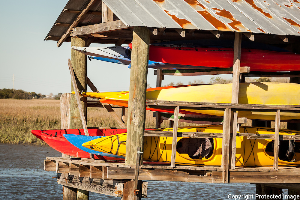 Colorful kayaks are stored on racks under a roofed shed on a dock.