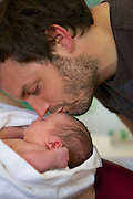 A new dad, Adam, looks at his baby daughter in the midwife led birth centre, Chelsea and Westminster Hospital, London.