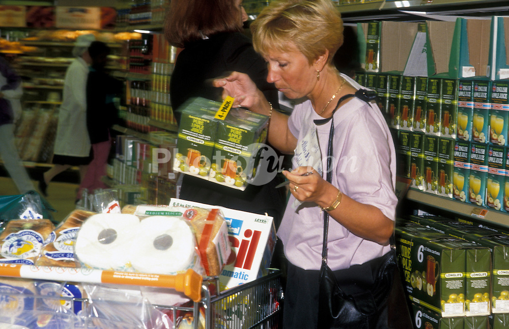 Female shopper with full trolley in Sainsburys supermarket UK