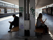 Two passengers wait for the next train in Cais do Sodré railway station.This photograph is part of a body of work about Lisbon, feelings, affections and loneliness. Is about a city depressed by the crisis, but even so, tolerant and cosmopolitan. This part of Lisbon, the old town near the river Tejo (Tagus), with his deep character, where local people meets foreigners and alternative ways of life mixes with shamefaced poverty, is sublime by its peculiar light.