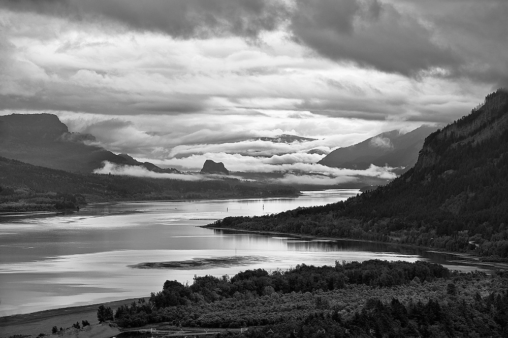 Columbia River Gorge, Oregon.<br /> Samuel Lancaster, the engineer for the Columbia River Highway, built Vista House on the promontory of Crown Point, some 700 sheer feet above the river.  It was a way station for travelers--&ldquo;an observatory from which the view both up and down the Columbia could be viewed in silent communion with the infinite.&rdquo;  Sounds dramatic, but the sensation of peering into the prehistoric here is palpable, despite the man-made intrusions.  The Columbia is so big it doesn't even seem to move.  It is the sky that moves, and ominously on this morning;  hopes for sunrise were pretty much dashed until a little break in the overcast transformed the vista for a brief few minutes, to commune with the infinite.