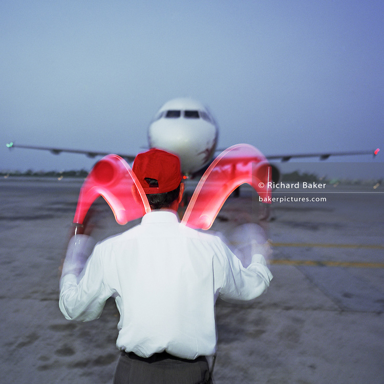 An airport worker employed by SABTCO guides an arriving Airbus onto its stand at Bahrain International Airport. The man carefully encourages the slow-moving flying machine using his illuminated sticks alerting the pilot in control of this commercial airliner to an exact stopping place after its taxiing from the runway. It is another hot day in this Gulf State, a key hub airport in the region, providing a gateway to the Northern Gulf. The airport is the major hub for Gulf Air which provides 52% of overall movements. It is also the half-way point between Western Europe and Asian destinations such as Hong Kong and Beijing. Picture from the 'Plane Pictures' project, a celebration of aviation aesthetics and flying culture, 100 years after the Wright brothers first 12 seconds/120 feet powered flight at Kitty Hawk,1903. .
