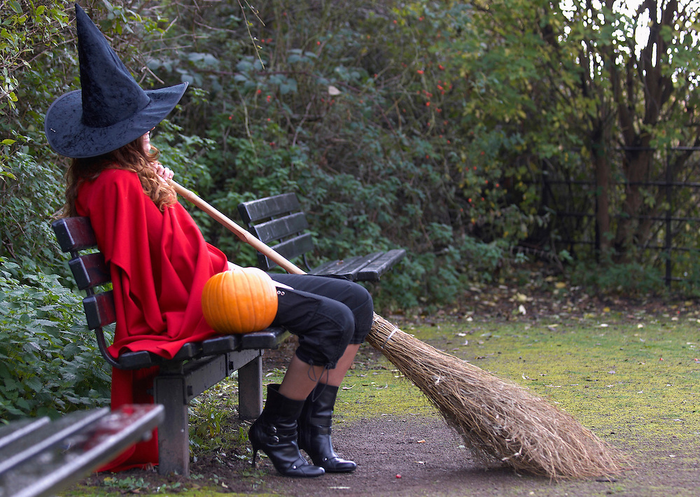 Modern witch sitting on a bench in a park<br />