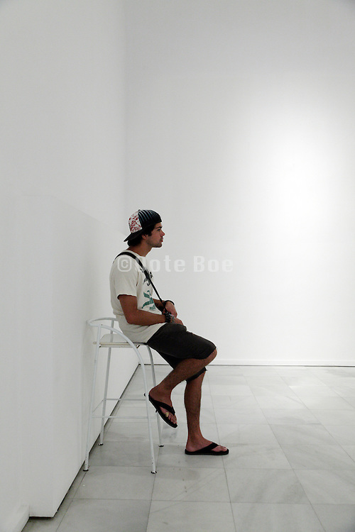 young adult male person sitting in an gallery space with empty walls
