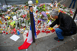 © Licensed to London News Pictures. 16/11/2015. Paris, France. Mourners visit memorial outside Le Petit Cambodge in Paris, France following the Paris terror attacks on Monday, 16 November 2015. Photo credit: Tolga Akmen/LNP
