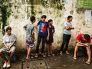06 OCTOBER 2016 - BANGKOK, THAILAND:  Residents of Pom Mahakan Fort relax against a city wall in the old fort. Evictions are continuing at a slow pace in Pom Mahakan Fort and as people move out their homes are destroyed to ensure new squatters don't move in. More than 40 families still live in the Pom Mahakan Fort community. Bangkok officials are trying to move them out of the fort and community leaders are barricading themselves in the fort. The residents of the historic fort are joined almost every day by community activists from around Bangkok who support their efforts to stay. City officials said recently that they expect to have the old fort cleared of residents and construction on the new park started by the end of 2016.     PHOTO BY JACK KURTZ