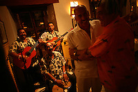 Two men greet each other as the band plays at La Vitrola, a popular restaurant in Cartagena's old city, on Thursday, August 21, 2008. (Photo/Scott Dalton)