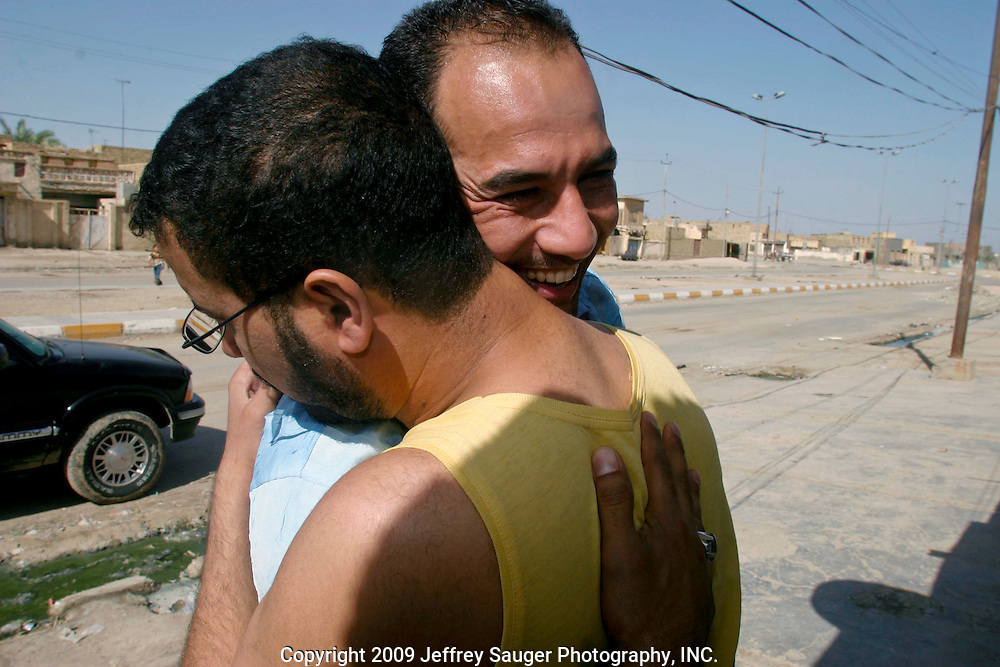 Emad Al-Kasid embraces childhood friend Jassem Mohammad Jassem in the neighborhood he grew up in on August 3, 2003. His family recently returned to their home village of Suq ash Shuyukh, about 20 miles southeast of Nasiriyah, Iraq, after fleeing for their lives for their part in the Southern uprising in 1991. After 3 years in a refugee camp in Rafha, Saudi Arabia, they settled in Dearborn, MI. This is the first time the family has been home in 13 years.