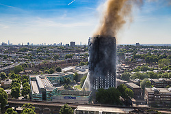 London, June 14th 2017. A fire rages through a residential tower block, Grenfell Tower, in Kensington, West London, with the entire building engulfed in flames. More than 200 firefighters are attending the incident and there are reports of people trapped inside. No figures are available as to casualties. The fire is visible right across the city.