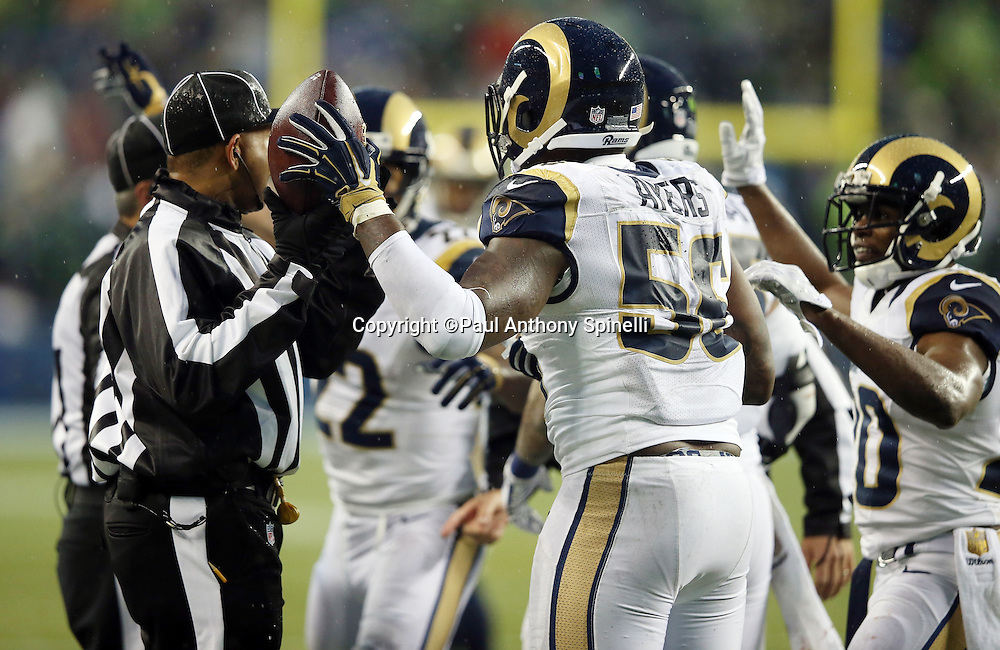 St. Louis Rams outside linebacker Akeem Ayers (56) holds the ball in the air after recovering a fumble by Seattle Seahawks quarterback Russell Wilson (3) on a hard hit by St. Louis Rams defensive end Eugene Sims (97) that stopped a potential scoring drive and a Seahawks comeback attempt late in the fourth quarter during the 2015 NFL week 16 regular season football game against the Seattle Seahawks on Sunday, Dec. 27, 2015 in Seattle. The Rams won the game 23-17. (©Paul Anthony Spinelli)