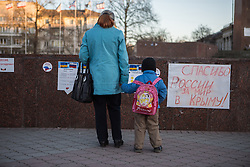 Crimea one day before the referendum. A mother and a child looks at a propaganda banner showing the benefits of joining Russia. Simferopol, . Saturday, 15th March 2014. Picture by Daniel Leal-Olivas / i-Images