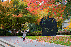 "United States, Washington, Bellevue, Girl jumpring rope near ""Thinker"" sculpture"