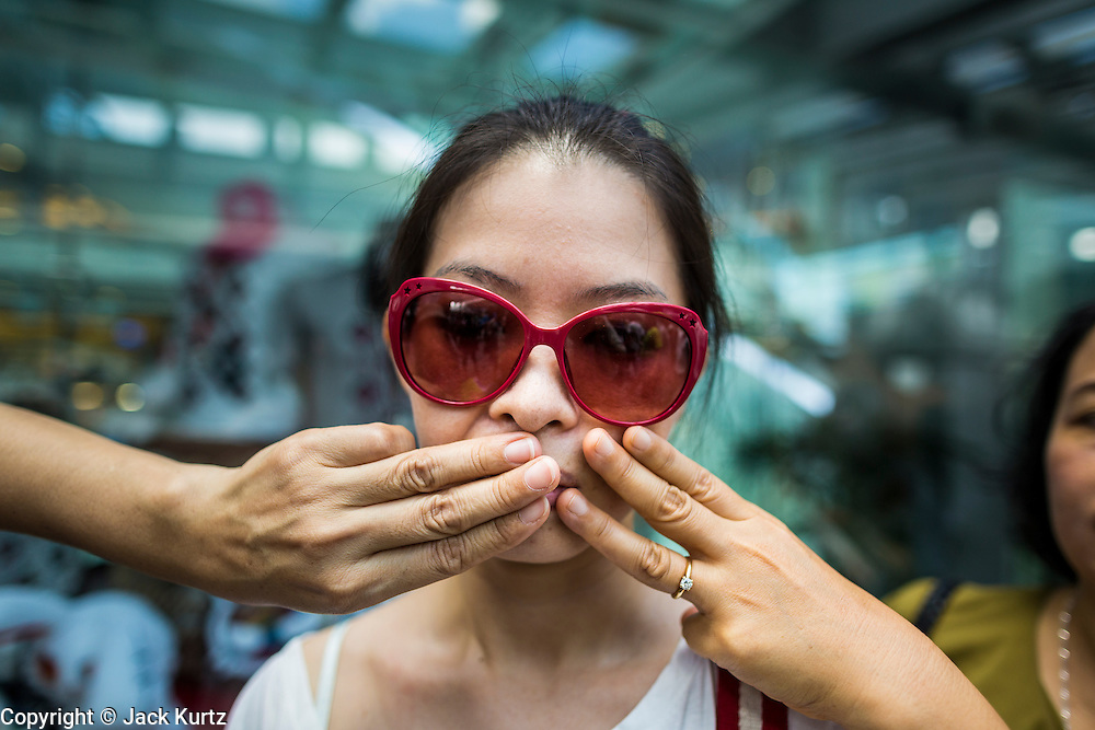"""01 JUNE 2014 - BANGKOK, THAILAND: A woman protests the loss of free speech with the help of her friends, who covered her mouth, during a protest against the Thai military coup at Terminal 21, a popular Bangkok shopping mall. The Thai army seized power in a coup that unseated a democratically elected government on May 22. Since then there have been sporadic protests against the coup. The protests Sunday were the largest in several days and seemed to be spontaneous """"flash mobs"""" that appeared at shopping centers in Bangkok and then broke up when soldiers arrived. Protest against the coup is illegal and the junta has threatened to arrest anyone who protests the coup. There was a massive security operation in Bangkok Sunday that shut down several shopping areas to prevent the protests but protestors went to malls that had no military presence.    PHOTO BY JACK KURTZ"""