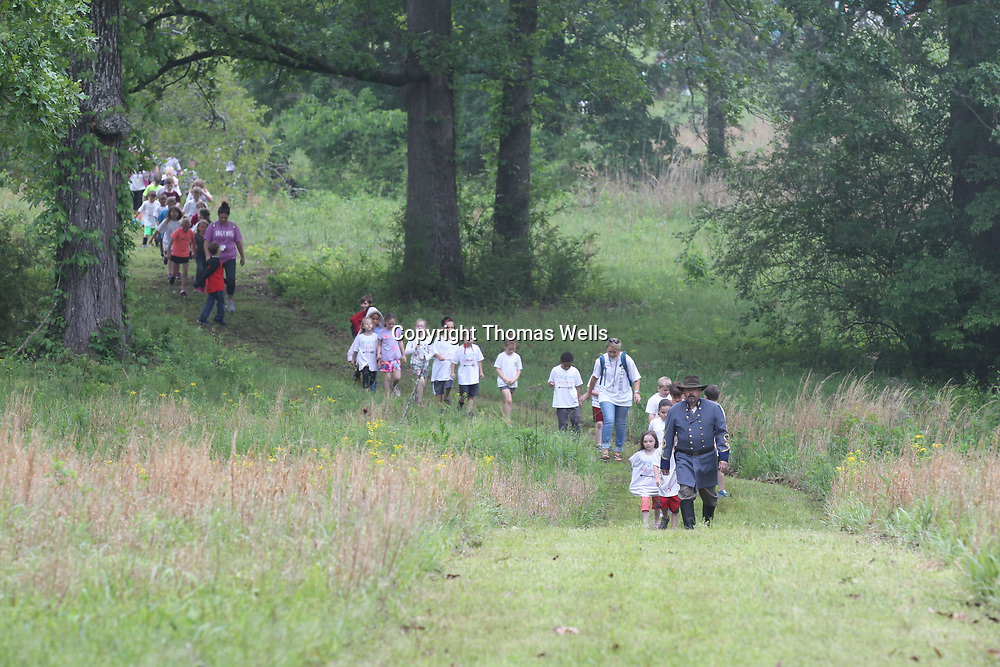 Bill Latham of Plantersville leads a long line of students from East Union through the woods to the Brice's Crossroads Discovery School Day on Friday.