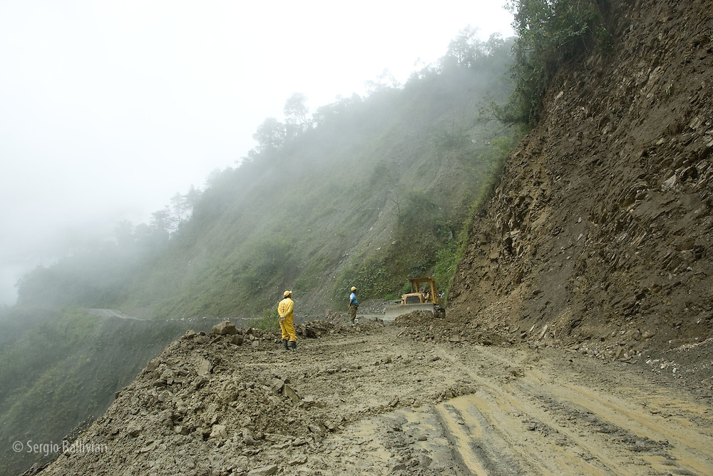 Road crews work with heavy contruction equipment to maintain a section of road that slides during the rainy season in the Yungas region, east of La Paz, Bolivia.