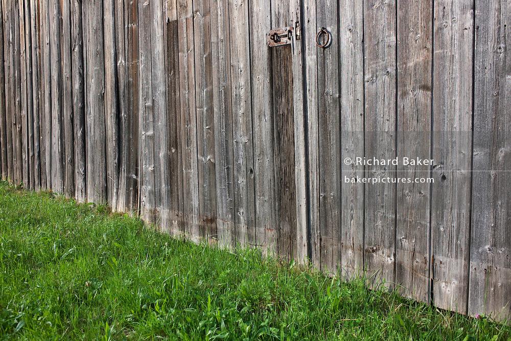 Weather-beaten wooden panels of barn doors in a meadow near village of Kälbermühle in German Black Forest region.
