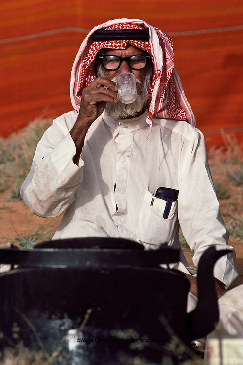 Bedouin elder Mohammed bin Salem Al Murrah drinking hot camel's milk mixed with tea for breakfast, Dahana Sands, Saudi Arabia