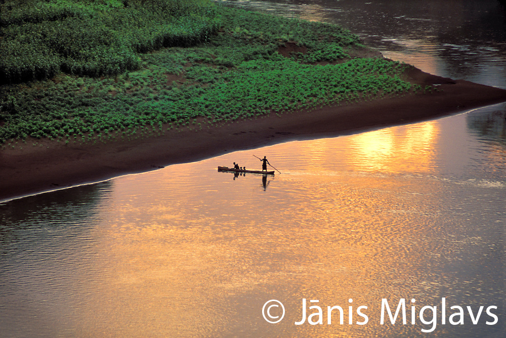 The sun sets on some Karo men piloting a dugout raft across the Omo River, near their village in Ethiopia, Africa.