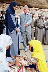 The Prince of Wales watches a young girl having a henna hand tattoo as he visits the Ras Al Shajar nature reserve in south east Oman during his official tour of the Middle East.