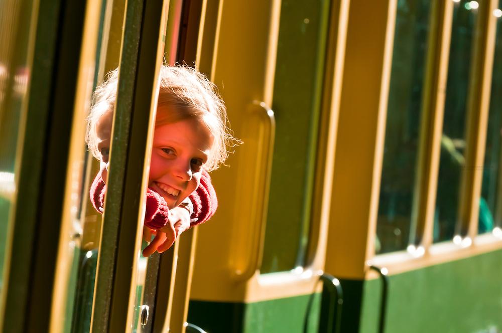 Young Swiss girl looking out of train window, Jungfrau Railway train descending from Wengernalp to Wengen, Swiss Alps, Canton Bern, Switzerland