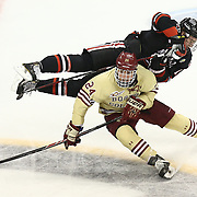John Stevens #18 of the Northeastern Huskies and Bill Arnold #24 of the Boston College Eagles collide during The Beanpot Championship Game at TD Garden on February 10, 2014 in Boston, Massachusetts. (Photo by Elan Kawesch)