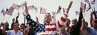 Happy mid adult man with crowd waving North American flags in background
