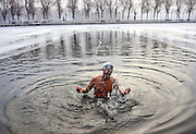 SHENYANG, CHINA - <br /> <br /> Winter Swimmers Exercise In frozen lake<br /> <br />  A man swims in a pool dug in the frozen river at Beiling Park in the smog in Shenyang, Liaoning Province of China. Winter swimmer exercised in the smog in Shenyang. At least 24 cities in North China issued red alerts on Dec 16 as heavy smog will shroud the country\'s northern regions in the following days<br /> ©Exclusivepix Media