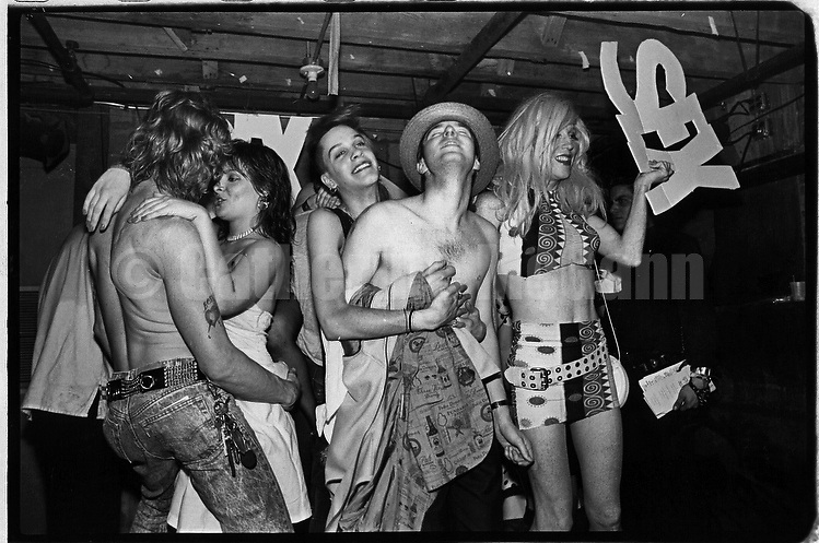 """June 15, 1988:  A  group of clubgoers having fun at the Celebrity Club at Tunnel nightclub in New York City, New York. Drag queen Lahoma Van Zandt on right holding a sign which says """"sex""""."""