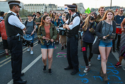 London, UK. 20th April 2019. Two police officers stand as they were as the XR Samba Band passes on Waterloo bridge, which has been blocked by climate change campaigners from Extinction Rebellion for six days. During that time, they have created a Garden bridge used for International Rebellion activities to demand urgent action to combat climate change by the British government.