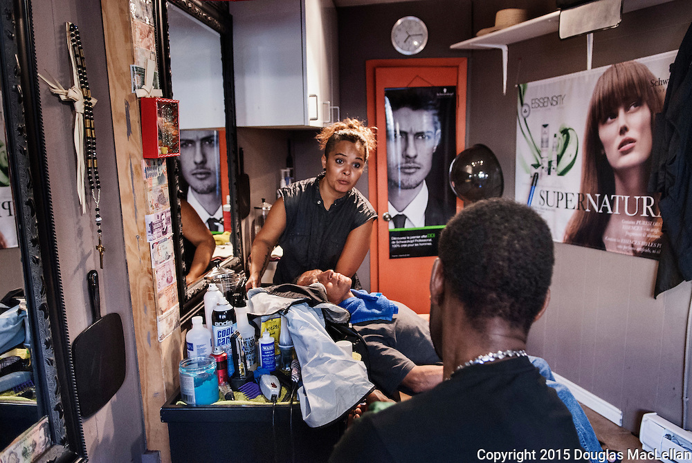 Xiomara Seth Condray, a second generation Canadian El Salvadoran, listens to a Jamaican worker while working on another man's hair in her small beauty shop in Leamington.
