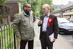 © Licensed to London News Pictures. 23/05/2015. London, UK. Labour Party candidate for Tower Hamlets Mayor, John Biggs speaks to a man on the street during canvassing on the Isle of Dogs in Tower Hamlets, east London. The Tower Hamlets Mayoral election will be re-run on 11th June after a High Court election petition found the previously elected mayor, Lutfur Rahman guilty of corrupt and illegal practices. Photo credit : Vickie Flores/LNP