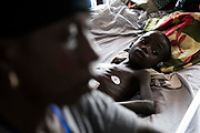 KABALA, SIERRA LEONE - Kadiatu Sesay, 7, looks on in bed as his grandmother Sallu Conteh takes care of him at Kabala General Hospital on November 10, 2017 in Kabala, Sierra Leone. Photo by Xaume Olleros / MSF