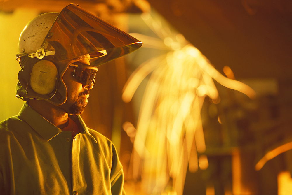 USA, Washington, Seattle, Worker monitors pouring of molten steel inside mill at Birmingham Steel Plant