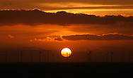 22/03/2014. North Wales, UK. The sun rises over the North Hoyle Offshore Wind Farm off the coast of North Wales this morning, 22nd March 2014. The Liverpool skyline can be seen on the horizon. Photo credit : Rob Arnold