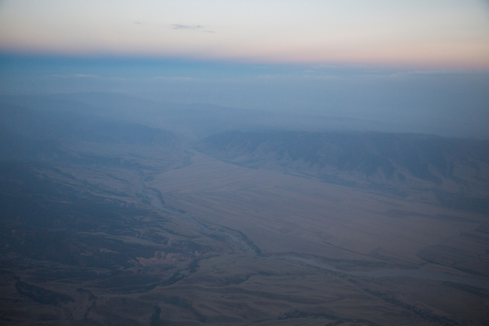 A view of a river valley flying over central Kyrgyzstan. The landscape here is harsh and parched in normal times. But  that has started to change as overgrazing has removed plants that hold topsoil. Heavy rains are now not absorbed causing floods and mudslides as the water rushes into flash floods in dry river beds.