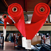 Two rolls of the red fireproof material Nomex made by the Du Pont corporation, is stored ready for tailoring by a bespoke seamstress at Dale Techniche, Nelson, Lancashire where every Winter, the elite 'Red Arrows', Britain's Royal Air Force aerobatic team place about 40 pilot suit orders and 180 blue (support ground crew) suits before their Summer air show season starts. Containing 5% Kevlar, all suits are made to fit exactly each team member. Fouteen different measurements are taken before the first suit is cut, each one requiring approximately three metres of dyed cloth. When a suit is complete, each one is signed inside by the machinist..The clothing factory also designs the Red Arrows badges, each requiring 15,000 stitches as well as suits for racing drivers, soldiers and pilots from other aerobatic teams. The Red Arrows have, since 1965 flown over 4,000 air shows in 52 countries.
