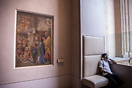 A man with a mask is having a rest sitting at the side of Botticelli's nativity.