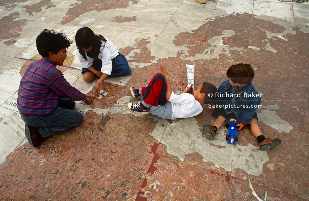 Children sit on street map of Europe, Africa and Asia laid across the pavement beneath Monument of Discoveries, Lisbon.