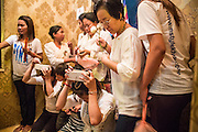 02 FEBRUARY 2013 - PHNOM PENH, CAMBODIA:  Cambodians cram into a small shrine near the Royal Palace to pray for former King Norodom Sihanouk. Much of Phnom Penh has been shut down to honor former King Norodom Sihanouk, who ruled Cambodia from independence in 1953 until he was overthrown by a military coup in 1970. Only bars, restaurants and hotels that cater to foreign tourists are supposed to be open. The only music being played publicly is classical Khmer music. Sihanouk died in Beijing, China, in October 2012 and will be cremated during a state funeral royal ceremony on Monday, Feb. 4.    PHOTO BY JACK KURTZ