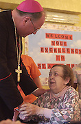 Archbishop Dolan greets a nursing home resident in Milwaukee in 2002. (Sam Lucero photo).