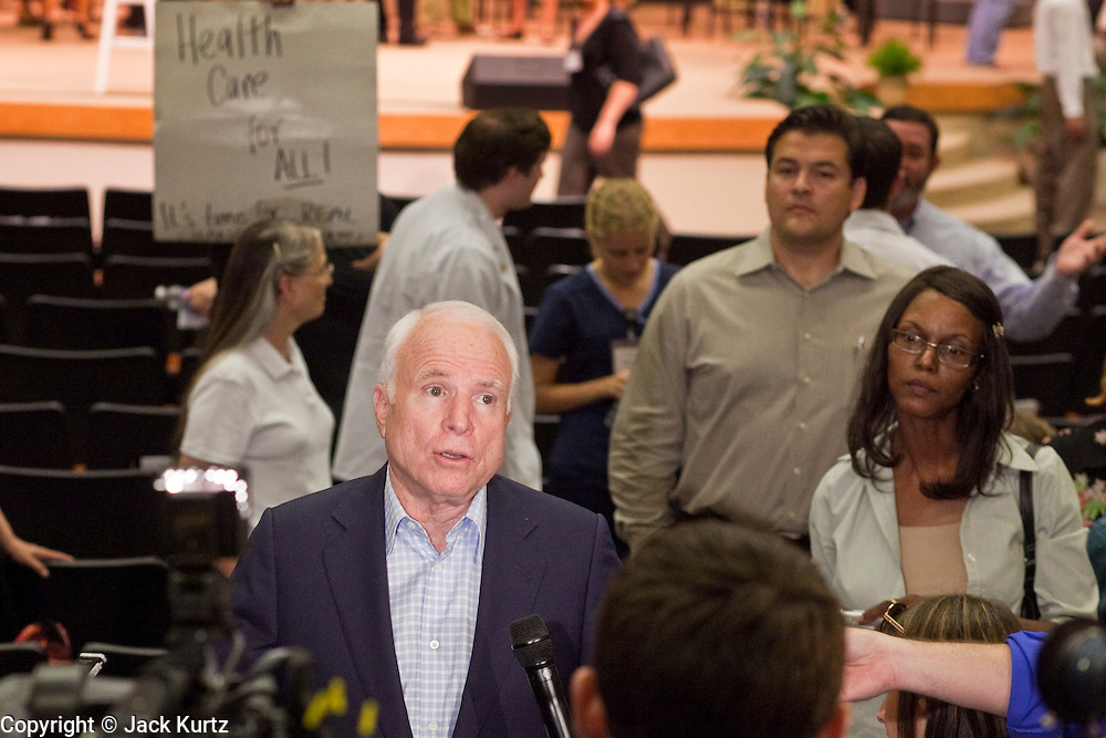 Aug 26, 2009 -- PHOENIX, AZ: A supporter of the public option holds up sign while Sen JOHN MCCAIN, who is opposed to the public option, gives television interviews after his town hall meeting at North Phoenix Baptist Church in Phoenix, AZ, Wednesday. Sen McCain hosted his second town hall meeting on health care in two days Wednesday. About 1,000 people attended the meeting. Although most were opposed to President Obama's health care proposals and supported Sen McCain, there was a large group who support the President's health care efforts.  Photo by Jack Kurtz