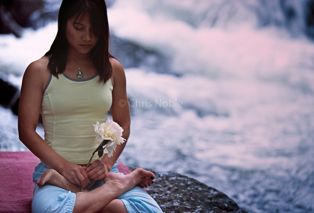 Yogini Ally Nguyen (Asian/American female, late twenties) meditates while holding a flower beside Little Cottonwood Creek in Utah's Wasatch Mountains.