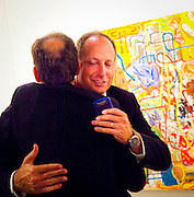 Two  men in suits embrace, while one seems to keep looking at his cell phone at Art Basel Miami Beach 2008