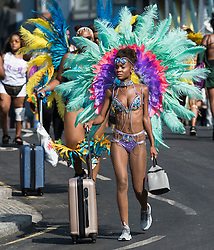 © Licensed to London News Pictures. 28/08/2017. London, UK. A carnival goer pushes her luggage to the second day of the 2017 Notting Hill carnival. The two day event is the second largest street festival in the world after the Rio Carnival in Brazil, attracting over 1 million people to the streets of West London. Photo credit: Ben Cawthra/LNP