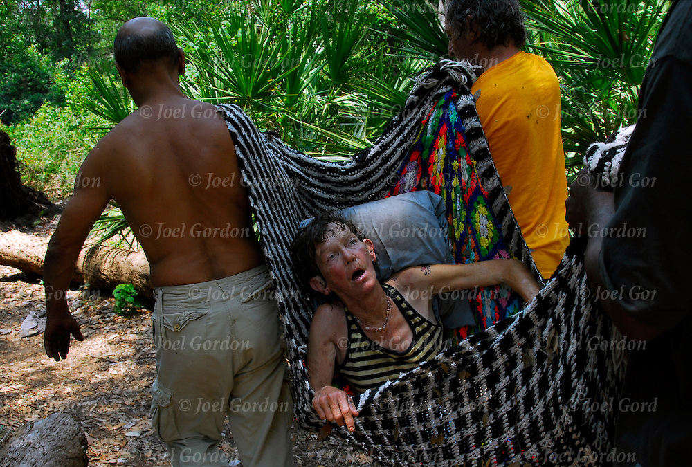 Call 911 and working together remove overdosed homeless woman out of wood to EMS.The Macon-Delta a camp of homeless people living in the woods of Orlando. They are called the tree people by other homeless street people.