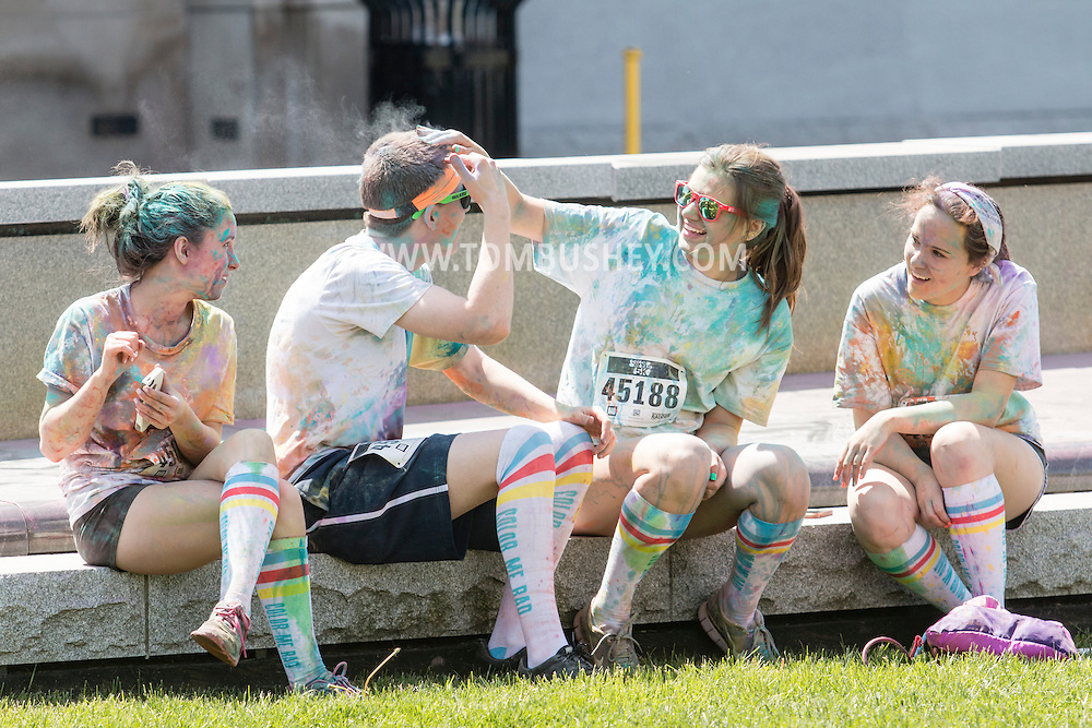 Scranton, Pa. - A girl rubs colorful powder out of a boy's hair after the Color Me Rad 5K color run on May 24, 2015.