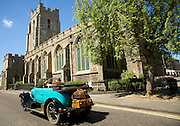 Classic veteran car passing Church of Saint Peter, Sudbury, Suffolk, England