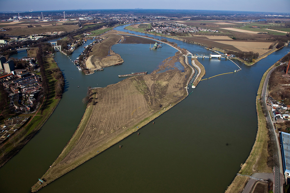 Nederland, Limburg, gemeente Maastricht, 07-03-2010; waterhuishouding van de Maas. Rechts de stuw bij Borgharen en de ingang van het Julianakanaal. Midden het eiland Bosscherveld wordt gedeeltelijk afgegraven, de Maas kan bij hoogwater in de toekomst ook over het eiland stromen. Direct naast het eiland een overlaat, deze ontlast - bij hoogwater - de stuw. Geheel links  het verbindingskanaal wat leidt naar de Zuid-Willemsvaart..De Maas vormt de grens met Belgie (l): Grensmaas..Water management of the Meuse. Weir at Borgharen (r) with entrance of Juliana canal. The island Bosscherveld (midle) is partially excavated, in the future the Meuse high water will flow over the island. Next to the island a spillway, functions in case of high waters as an extra relieve for the weir at Borgharen. Very left the channel which leads to the South Willemsvaart. .The Meuse forms the border with Belgium (l): Grensmaas ('Border Meuse').luchtfoto (toeslag), aerial photo (additional fee required).foto/photo Siebe Swart