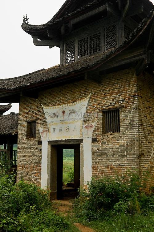 Entrance tower of a wind and rain bridge sitting in the fields of fuchuan yao autonomous region, China.